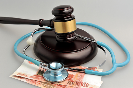 paid medicine: Stethoscope with judge gavel, money on gray background Stock Photo