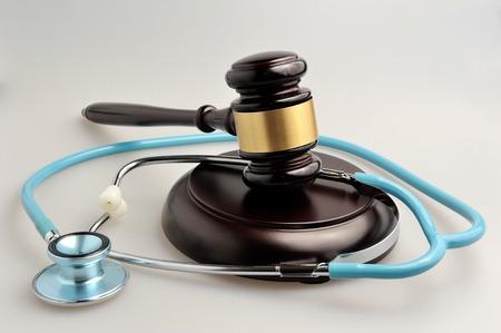 Stethoscope with judge gavel on gray background