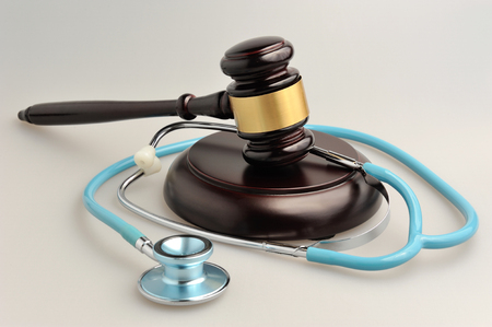 Stethoscope with judge gavel on gray background