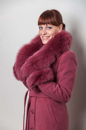 A smiling girl in a coat with a fur collar