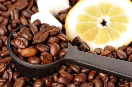 grains of coffee: Granos de caf� en una cuchara de medir, lim�n y az�car