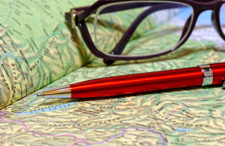 remoteness: Ballpoint pen and glasses lie on geographical atlas