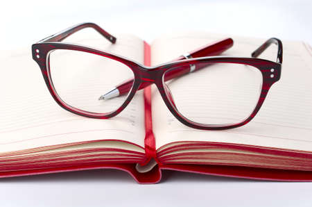 date book: Red Daily planner with eyeglasses and pen, closeup Stock Photo
