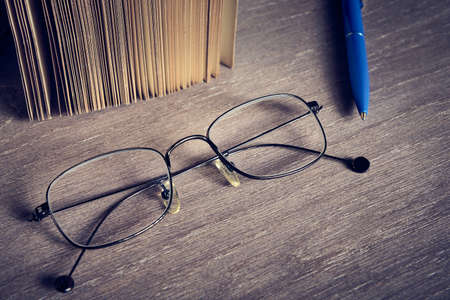 Stylish glasses lie on a wooden surface, vintage