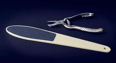 Metal nippers for nails and grater for heels on dark background