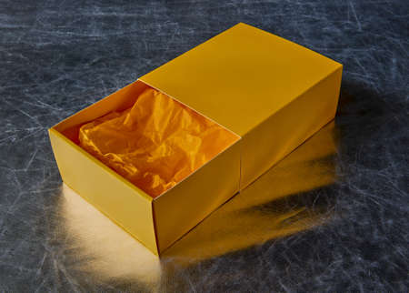 View of an open yellow gift box with packaging paper inside on a silver background