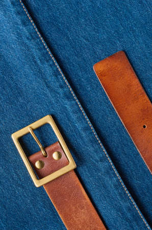 Leather belt on the background of denim fabric