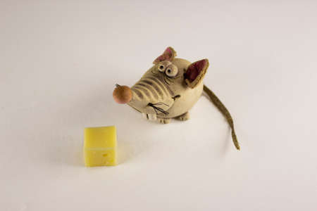 Figures Of Rats And A Piece Of Cheese On White Background. Statuette of mouse, close up. New Year concept. Selective focus. Stock Photo