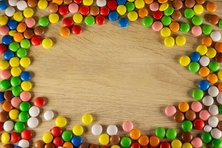 Colorful dragee beans in the shape of framework on a brown background. Decoration background. Closeup.