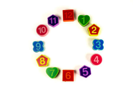 Colorful bright educational toys in the form of lacing for children.Educational toys. Colorful wooden geometric shapes pattern with numbers on white background. Copy Space Imitation clock.