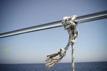 Marine Knot Detail Stainless Steel Boat Railing. Marine Fender Knot Around Boat Lee. Close-up nautical knot rope on sail boat