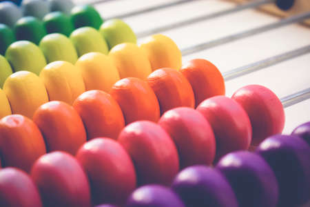 Multi-colored designer background. Calculating Colorful wooden rainbow abacus for number calculation. Close up wooden abacus on white background. Mathematics learning concept