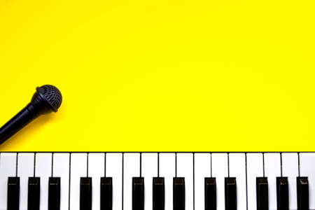 Top view piano keys over yellow background. Pianist musician, pianist concept. Piano And Microphone. Music Keyboard. Copy space Foto de archivo