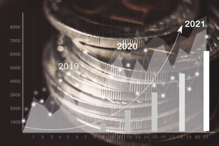 Coins stacked on each other in different positions on dark background. Earnings chart for 2021. Business financial concept