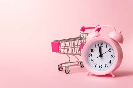 Close-Up Of Alarm Clock and Shopping Cart on Pink Background. Top view, flat lay with copy space