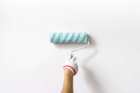 Hand holds paint roller and painting a White wall. Decorator's hand painting wall with roller Stock fotó