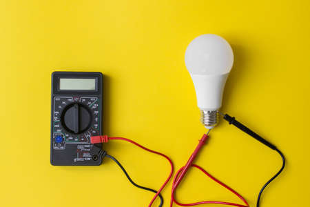 Dark Digital multimeter with probes and LED bulb on yellow background. Power saving concept. A multimeter is an electronic measuring instrument Archivio Fotografico