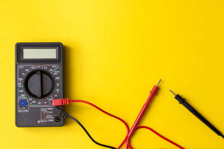 Digital multimeter with probes and backlit display on a yellow background. A multimeter or a multitester is an electronic measuring instrument