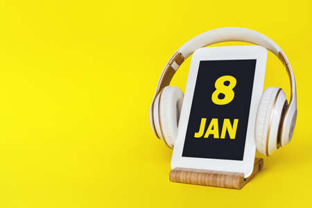 January 8th. Day 8 of month, Calendar date. Stylish headphones and modern tablet on yellow background. Space for text. Education, technology, lifestyle. Winter month, day of the year concept Фото со стока