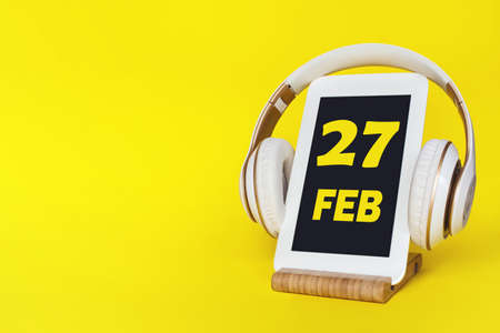 February 27th. Day 27 of month, Calendar date. Stylish headphones and modern tablet on yellow background. Space for text. Education, technology, lifestyle. Winter month, day of the year concept