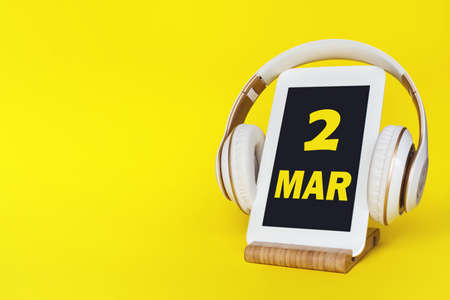 March 2nd. Day 2 of month, Calendar date. Stylish headphones and modern tablet on yellow background. Space for text. Concept education, technology, lifestyle. Spring month, day of the year concept