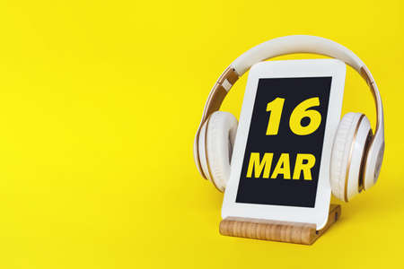 March 16th. Day 16 of month, Calendar date. Stylish headphones and modern tablet on yellow background. Space for text. Concept education, technology, lifestyle. Spring month, day of the year concept