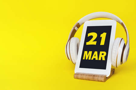March 21st. Day 21 of month, Calendar date. Stylish headphones and modern tablet on yellow background. Space for text. Concept education, technology, lifestyle. Spring month, day of the year concept
