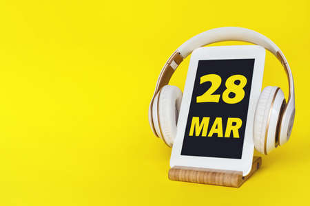 March 28th. Day 28 of month, Calendar date. Stylish headphones and modern tablet on yellow background. Space for text. Concept education, technology, lifestyle. Spring month, day of the year concept