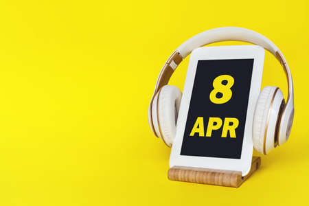 April 8th. Day 8 of month, Calendar date. Stylish headphones and modern tablet on yellow background. Space for text. Concept education, technology, lifestyle. Spring month, day of the year concept