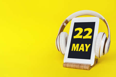 May 22nd. Day 22 of month, Calendar date. Stylish headphones and modern tablet on yellow background. Space for text. Concept education, technology, lifestyle. Spring month, day of the year concept