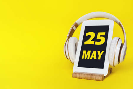 May 25th. Day 25 of month, Calendar date. Stylish headphones and modern tablet on yellow background. Space for text. Concept education, technology, lifestyle. Spring month, day of the year concept