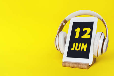June 12nd. Day 12 of month, Calendar date. Stylish headphones and modern tablet on yellow background. Space for text. Education, technology, lifestyle. Summer month, day of the year concept