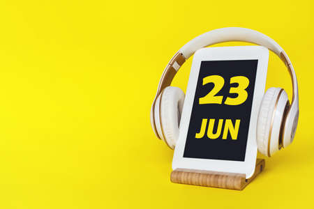 June 23rd. Day 23 of month, Calendar date. Stylish headphones and modern tablet on yellow background. Space for text. Education, technology, lifestyle. Summer month, day of the year concept Фото со стока