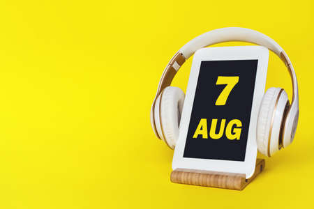 August 7th. Day 7 of month, Calendar date. Stylish headphones and modern tablet on yellow background. Space for text. Education, technology, lifestyle. Summer month, day of the year concept