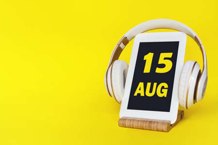 August 15th. Day 15 of month, Calendar date. Stylish headphones and modern tablet on yellow background. Space for text. Education, technology, lifestyle. Summer month, day of the year concept Фото со стока