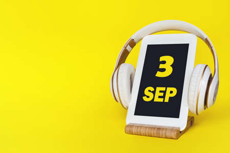 September 3rd. Day 3 of month, Calendar date. Stylish headphones and modern tablet on yellow background. Space for text. Education, technology, lifestyle. Autumn month, day of the year concept