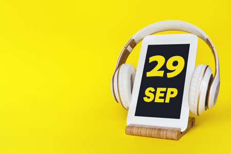 September 29th. Day2 9 of month, Calendar date. Stylish headphones and modern tablet on yellow background. Space for text. Education, technology, lifestyle. Autumn month, day of the year concept