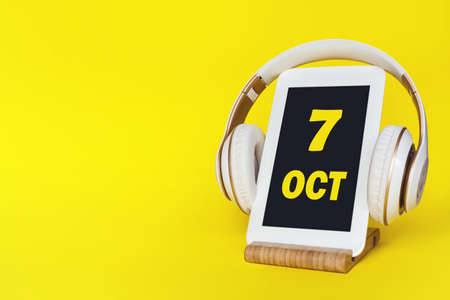 October 7th. Day 7 of month, Calendar date. Stylish headphones and modern tablet on yellow background. Space for text. Education, technology, lifestyle. Autumn month, day of the year concept