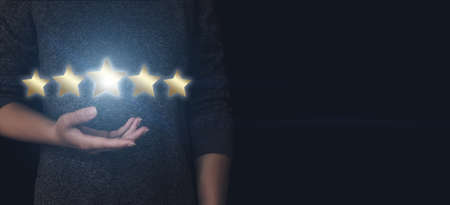 The concept of assessment. Hand pointing to five stars to increase the company's rating, increase the rating. The client's hand gives a five-star rating. Rating services, the concept of satisfaction Reklamní fotografie