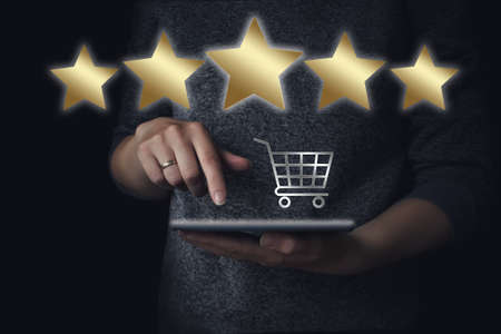 Retail consumer buying online assessment and review concept. Hand hold tablet with gologram Small supermarket grocery cart for shopping toy and 5 stars rating on dark background