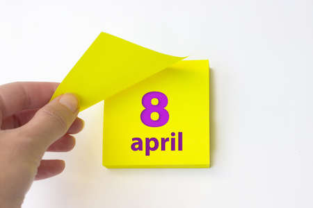 April 8th. Day 8 of month, Calendar date. Hand rips off the yellow sheet of the calendar. Spring month, day of the year concept