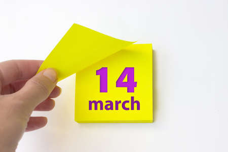 March 14th. Day 14 of month, Calendar date. Hand rips off the yellow sheet of the calendar. Spring month, day of the year concept