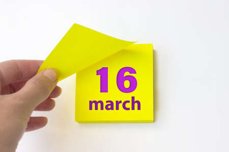 March 16th. Day 16 of month, Calendar date. Hand rips off the yellow sheet of the calendar. Spring month, day of the year concept