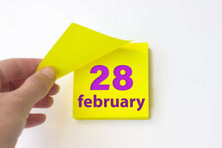 February 28th. Day 28 of month, Calendar date. Hand rips off the yellow sheet of the calendar. Winter month, day of the year concept