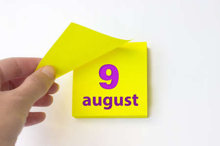 August 9th. Day 9 of month, Calendar date. Hand rips off the yellow sheet of the calendar. Summer month, day of the year concept