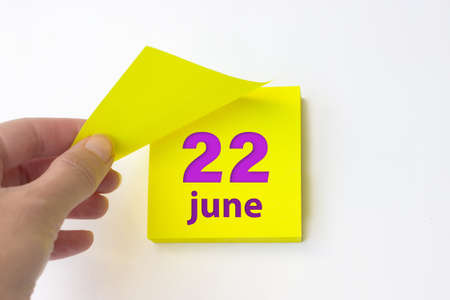 June 22nd. Day 22 of month, Calendar date. Hand rips off the yellow sheet of the calendar. Summer month, day of the year concept