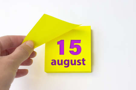 August 15th. Day 15 of month, Calendar date. Hand rips off the yellow sheet of the calendar. Summer month, day of the year concept