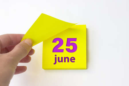 June 25th. Day 25 of month, Calendar date. Hand rips off the yellow sheet of the calendar. Summer month, day of the year concept