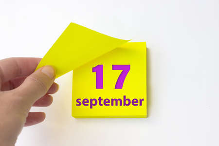 September 17th. Day 17 of month, Calendar date. Hand rips off the yellow sheet of the calendar. Autumn month, day of the year concept