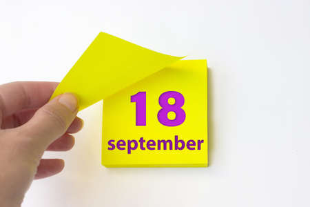 September 18th. Day 18 of month, Calendar date. Hand rips off the yellow sheet of the calendar. Autumn month, day of the year concept